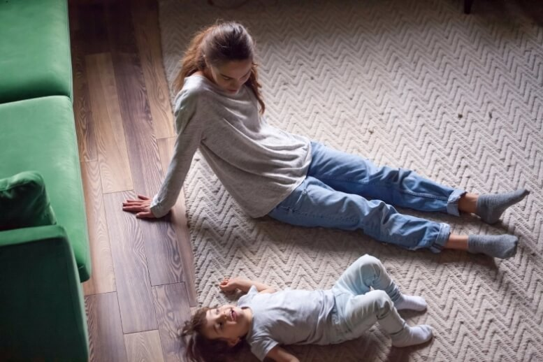 Moeder en kind spelen op de vloer